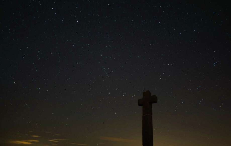 A meteor streaks across the night sky above New Ralph's Cross on Tueday on the North Yorkshire Moors, United Kingdom. The Perseid Meteor shower is visible from mid-july each year with peak activity being between the 9th and 14th of August. During the peak, the rate of meteors can reach 60 or more per hour. They can be seen all across the sky as they gradually fall away from the tail of the Swift-Tuttle comet. Photo: Ian Forsyth, Getty / 2013 Ian Forsyth