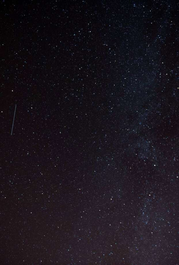 A Perseid meteor streaks across the night sky during the peak of the annual Perseid meteor shower on Monday in London, England. The annual display, known as the Perseid shower because the meteors appear to radiate from the constellation Perseus in the northeastern sky, is a result of Earth's orbit passing through debris from the comet Swift-Tuttle. Photo: Ollie Millington, Getty / 2013 Ollie Millington
