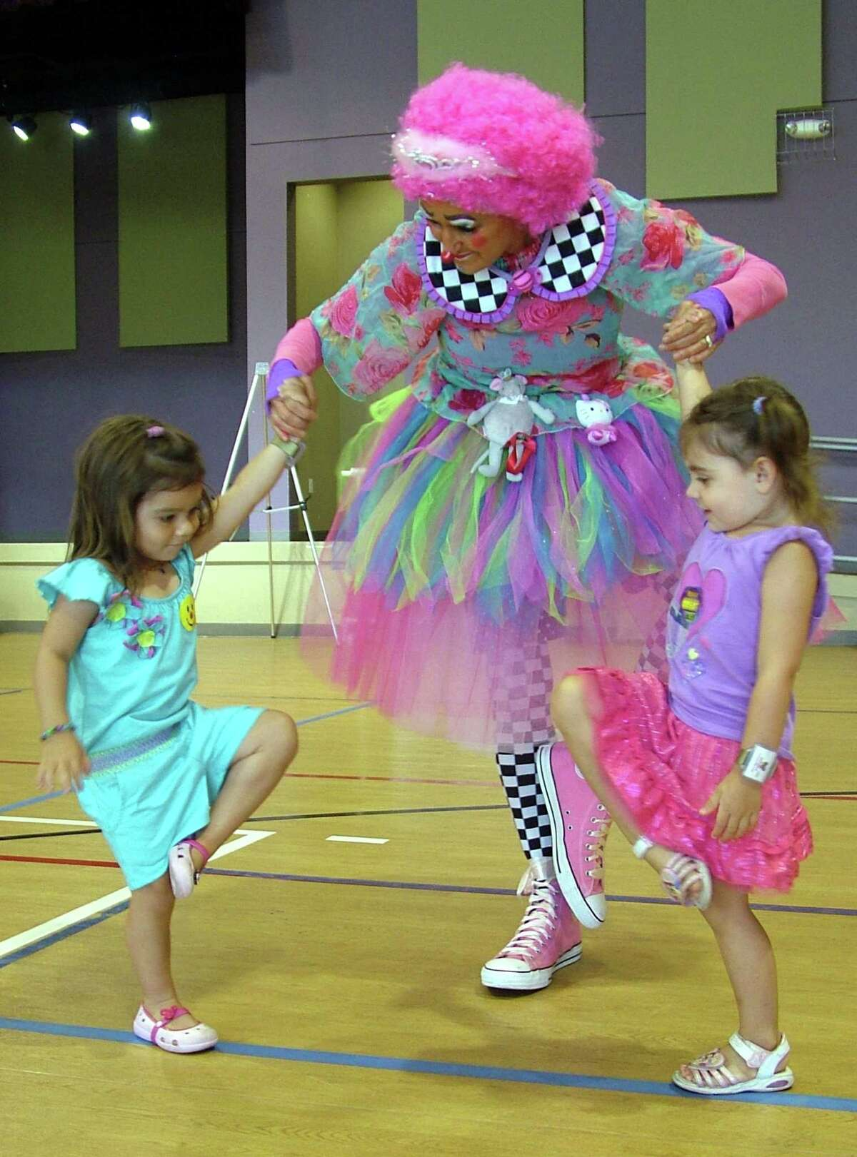 Two-year-old Noa Forrest of Windermere, Fla., (left) and Hadley Lamar of Live Oak enjoy a dance Saturday with Tutu the clown of the Jolly Joeys Clown Alley organization at Morgan's Wonderland.
