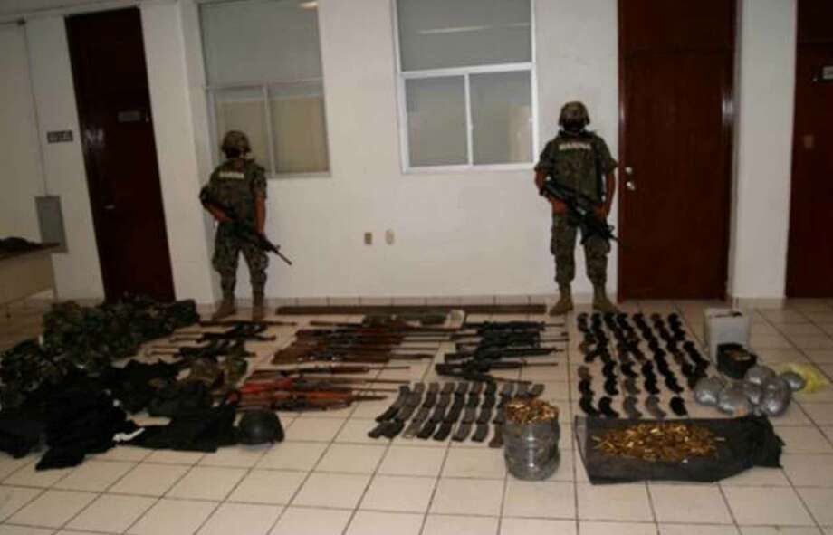In this image released by Mexico's Navy, mexican Navy sailors guard the weapons seized after a gun fight between the navy and drug cartel gunmen after the killing of 72 migrants in San Fernando, eastern Mexico, Tuesday, Aug. 24, 2010. A Mexican drug cartel massacred 72 Central and South American migrants within 100 miles of the U.S. border that they were trying to reach, according to Lala Pomavilla who said to be a survivor who escaped and stumbled wounded to a highway checkpoint where he alerted marines. Lala Pomavilla told investigators that his captors identified themselves as members of the Zetas drug gang, said Vice Adm. Jose Luis Vergara, a spokesman for the Mexican Navy. (AP Photo/ Mexico's Secretary Navy) Photo: Mexico's Secretary Navy, ASSOCIATED PRESS / AP
