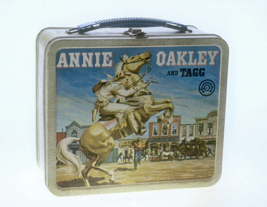 """Whether you go vintage, pseudo-vintage, space-age or international, your lunch box can make you feel good or bad about lunch. Check out these different styles of sandwich-toting tools over the years.Undated file photo of a Annie Oakley lunch box, part of the """"Lunch Box Memories"""" exhibit at the Lafayette Natural History Museum in 2002. The box was the first television-based metal lunch box targeting girls. Photo: AP / SMITHSONIAN"""