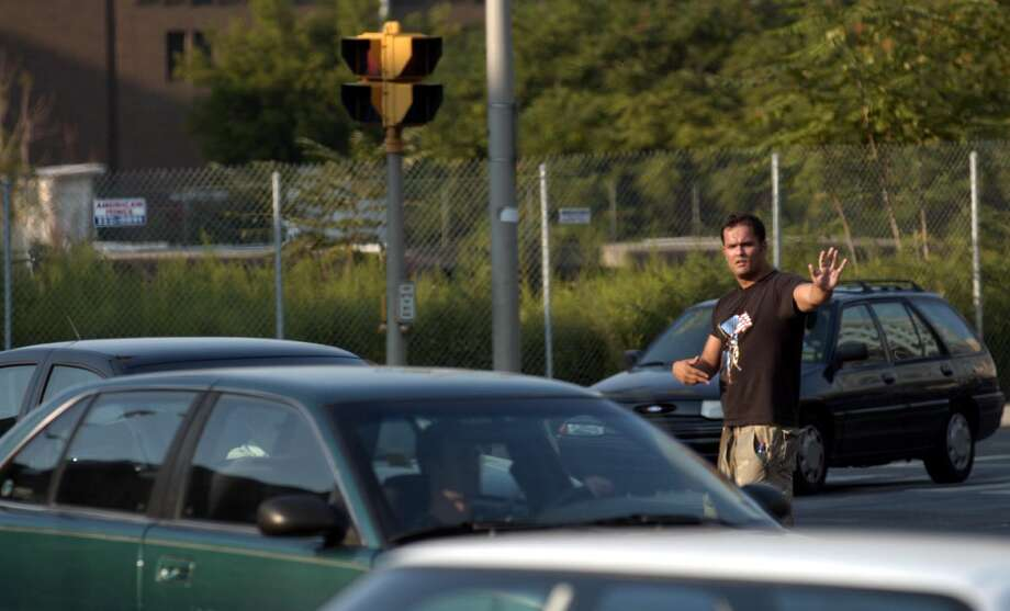 Stamford_081403_The blackout of 2003 wreaks havoc on the sleepy streets of corporate mecca Stamford, Conn. Here, a Good Samaritan directs traffic at the intersection of Tresser Blvd. and Canal St. in Stamford. Andrew Sullivan/Staff photo Photo: File, Stamford Advocate / Stamford Advocate