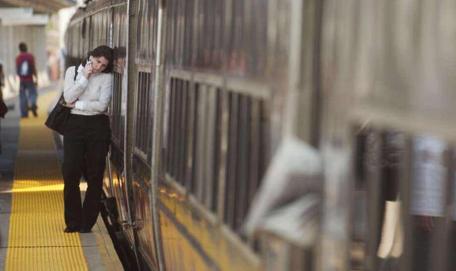 Alison McKnight of New York City, leans against a stalled Metro North train at the Stewart McKinney Transportation Center in Stamford. Mcknight couldn't get a cell phone signal. Photo: Andrew Sullivan, File