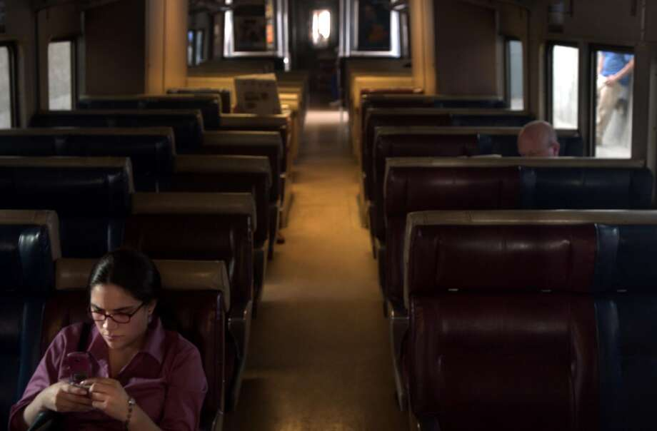Commuters sit in a stalled and darkened Metro North train in Stamford shortly after the blackout Thursday afternoon. Most took the inconvenience in stride, trying to get updates and remain as comfortable as possible. Photo: Andrew Sullivan, File