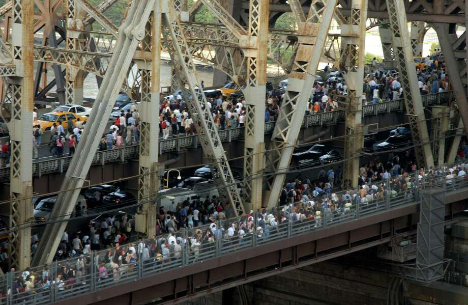 Pedestrians and traffic leaving downtown Manhattan crossing the Queensboro Bridge after the onset of the largest power blackout in American history, August 14, 2003. More than 50 million people were affected by the outage, in Toronto, Detroit, Cleveland and New York City. Photo: Robin Platzer, File / FilmMagic