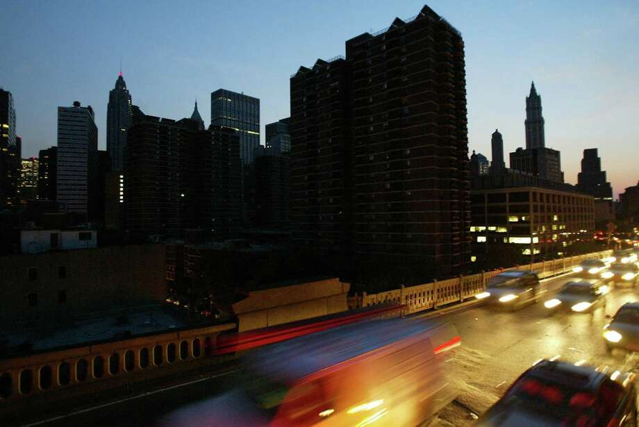 Cars head over the Brooklyn Bridge beside a blacked out New York City skyline August 14, 2003 during a power outage. The New York City comptroller William Thompson estimated August 18, 2003 that the blackout cost the city $1.05 billion including $250 million in perishable food that had to be discarded. The cost does not include overtime to city workers or lost tax revenue. Photo: Spencer Platt, File / 2003 Getty Images