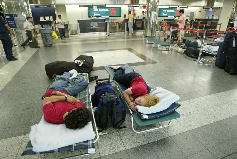 Stranded Air Canada passengers rest on cots inside LaGuardia Airport August 15, 2003 in New York City. Major airlines were forced to delay or cancel flights due to a huge power outage August 14 in the northeastern U.S. and parts of Canada. Photo: Anthony Correia, File / 2003 Getty Images