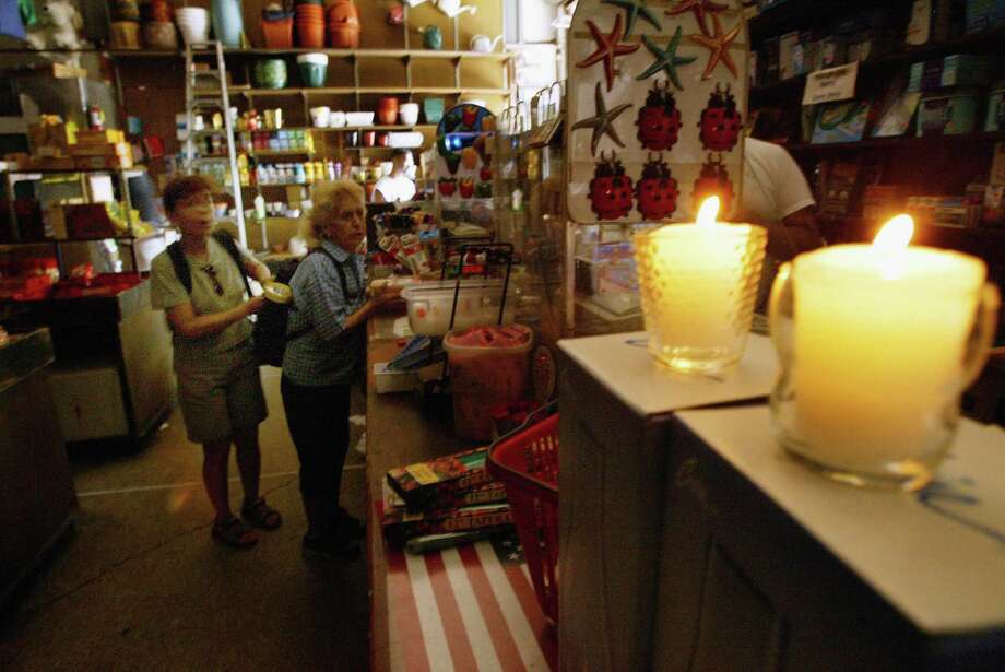 People shop in a store by candlelight in New York City the day after one of the largest blackouts in the nations history August 15, 2003 In New York. Power went out across large parts of the East Coast of North America Thursday afternoon. Photo: Spencer Platt, File / 2003 Getty Images