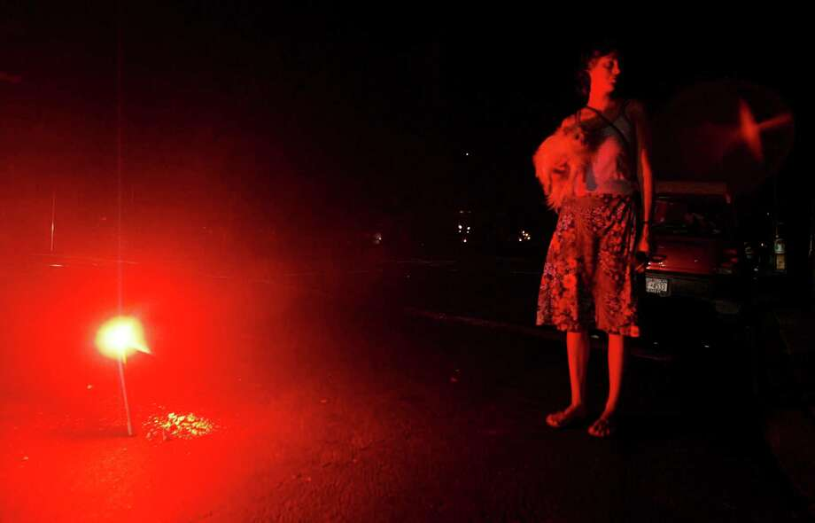 A woman holds her dog whilst she stands next to a flare during a massive blackout August 15, 2003 in New York City. Power is slowly returning to certain parts of the city. Photo: Mario Tama, File / 2003 Getty Images