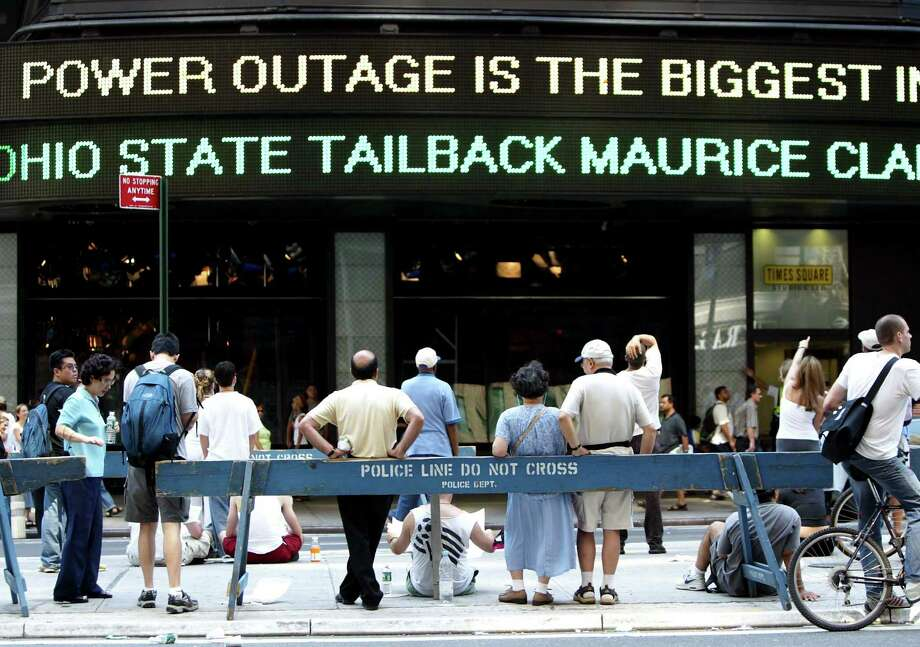 "People watch a news ticker reading ""Power Outage is The Biggest in US History"" in Times Square during a massive blackout August 15, 2003 in New York City. Power is slowly returning to certain parts of the city. Photo: Mario Tama, File / 2003 Getty Images"