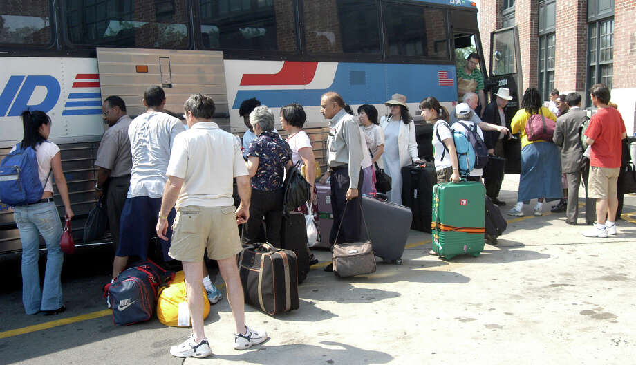 People line-up to stow their luggage as they board a Greyhound bus at the New Haven train station to take them to New York due to the problems caused to train service as a result of power outage, Aug. 14th, 2003. Photo: File Photo/Jeff Bustraan, File / Connecticut Post File Photo