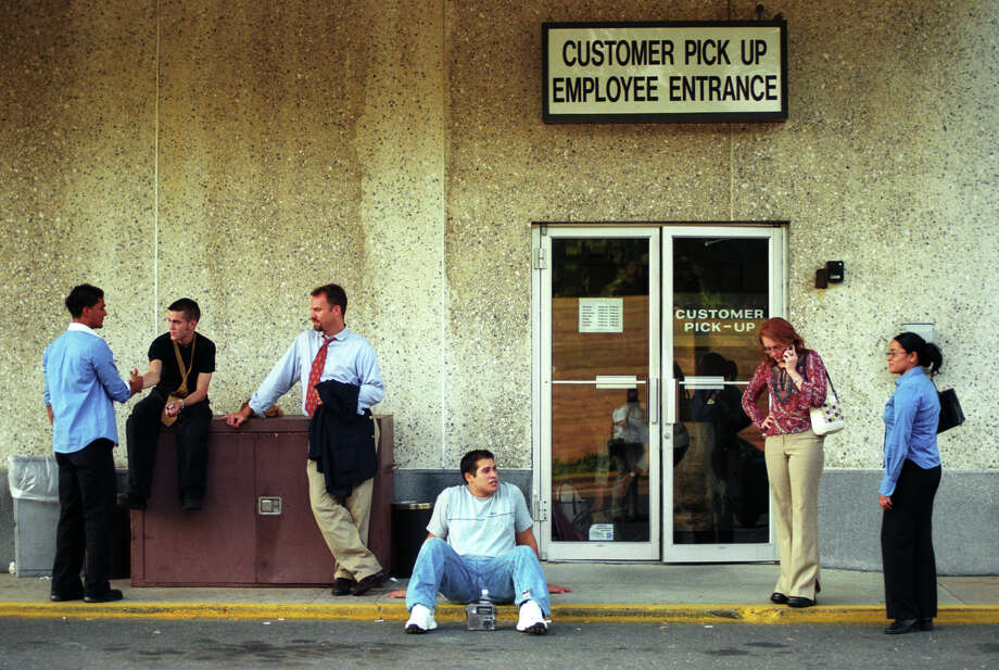 "Sales manager Dana Cote (second from right) calls her home in Milford, Conn., to see if they are out of power, while she and other Macy's employees wait for rides home in the heat outside the Trumbull Mall after the stores were shut down due to the power outage August 14, 2003. According to Christine Idler, general manager of Macy's, the power went out temporarily around 4:15 pm, and by 4:30 the store was pitch black. The employees quickly helped evacuate people out down the escalators. ""Our concern was the safety of getting everyone out,"" said Idler, ""it was a very smooth evacuation."" Photo: File Photo/Andrea A. Dixon, File / Connecticut Post File Photo"
