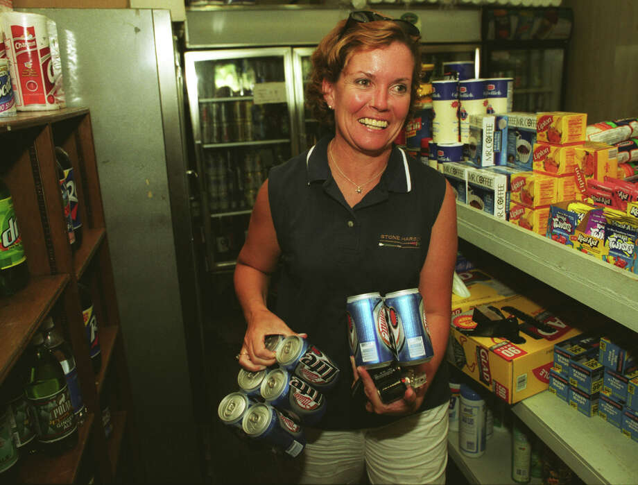 "Mary Kleps, of Bridgeport, grabs ""D"" batteries and cold beer in the darkened aisles of the Black Rock Market, in Bridgeport, Conn. during the power outtage Aug. 14, 2003. Finding the silver lining in the whole mess, Kleps was planning an outdoor barbecue for dinner. Photo: Brian A. Pounds, File / Connecticut Post"