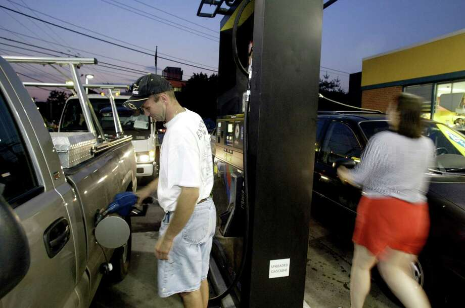 Chester Mocrzke, left, of Fairfield pumps gas at a Mobile gas station in Fairfield, Conn., during a power failure Aug. 14th, 2003. The outage shut down two out of the 4 gas pumps. Photo: File Photo/Mike Ross, File / Connecticut Post File Photo