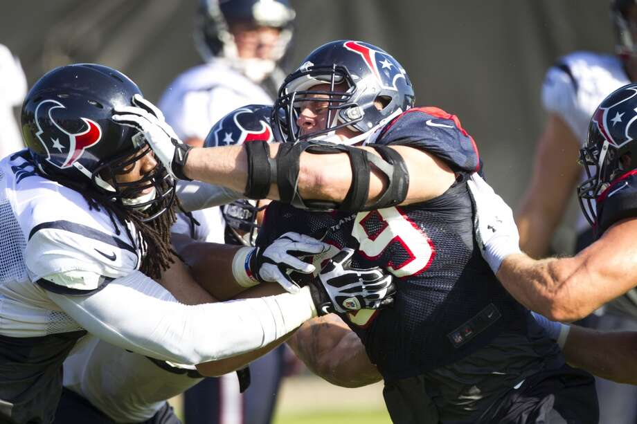 Defensive end J.J. Watt (99) battles with tackle Derek Newton (75) on a pass rush drill during Texans training camp on Tuesday. Photo: Brett Coomer, Chronicle