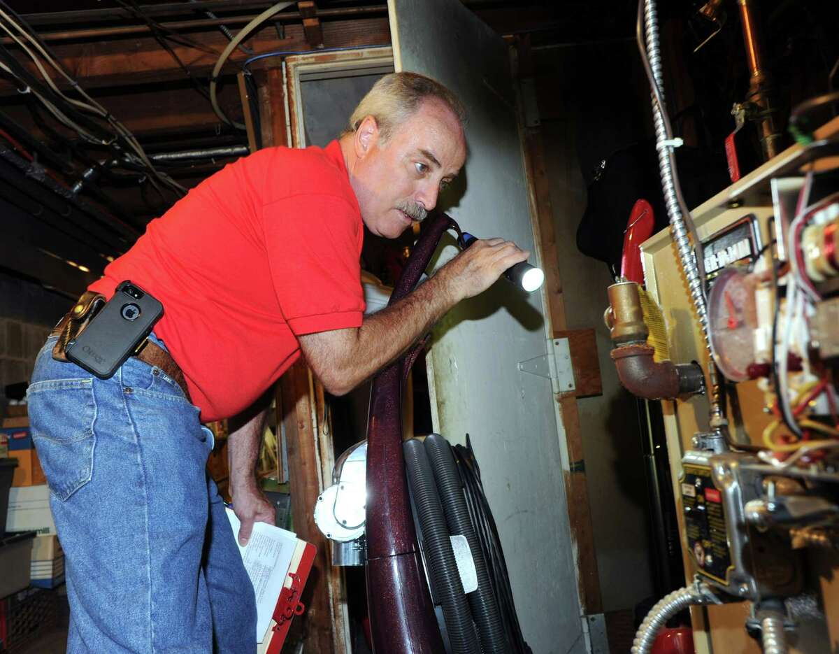 G. Neil Scott inspects the oil burner in the basement at a McArthur Lane home in Stamford, Tuesday, August 13, 2013. Scott is the owner of Scott and Scott Home Inspection Services Inc., of Stamford.