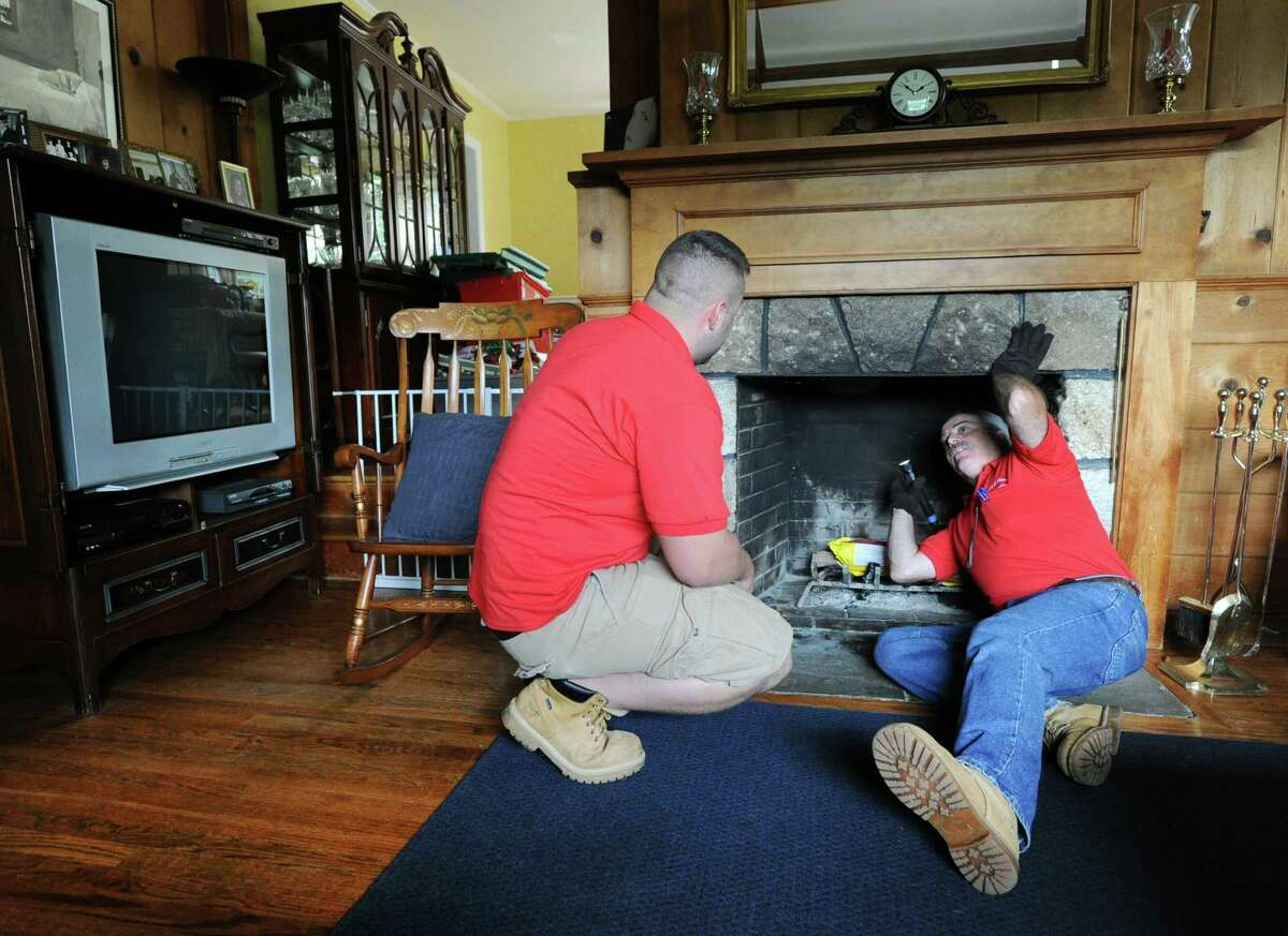 G. Neil Scott, right, and his son, Neil Scott, inspect the fireplace at a McArthur Lane home in Stamford, Tuesday, August 13, 2013. G. Neil Scott is the owner of Scott and Scott Home Inspection Services Inc., of Stamford.