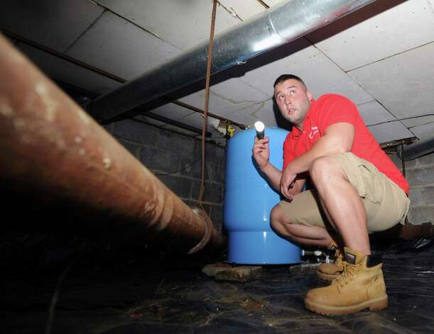 Neil Scott inspects piping in a crawl-space at a McArthur Lane home in Stamford, Tuesday, August 13, 2013. Scott's father, G. Neil Scott is the owner of Scott and Scott Home Inspection Services Inc., of Stamford. Photo: Bob Luckey / Greenwich Time