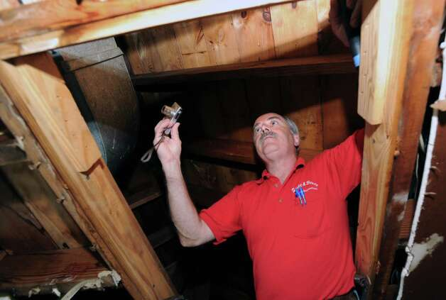 G. Neil Scott inspects the attic above a garage at a McArthur Lane home in Stamford, Tuesday, August 13, 2013. Scott is the owner of Scott and Scott Home Inspection Services Inc., of Stamford. Photo: Bob Luckey / Greenwich Time