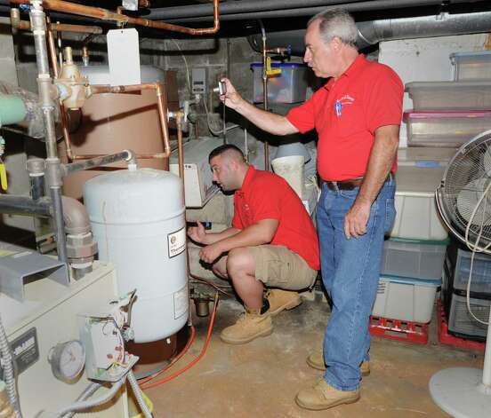 G. Neil Scott, right, and his son, Neil Scott, inspect the water heater in the basement at a McArthur Lane home in Stamford, Tuesday, August 13, 2013. G. Neil Scott is the owner of Scott and Scott Home Inspection Services Inc., of Stamford. Photo: Bob Luckey / Greenwich Time