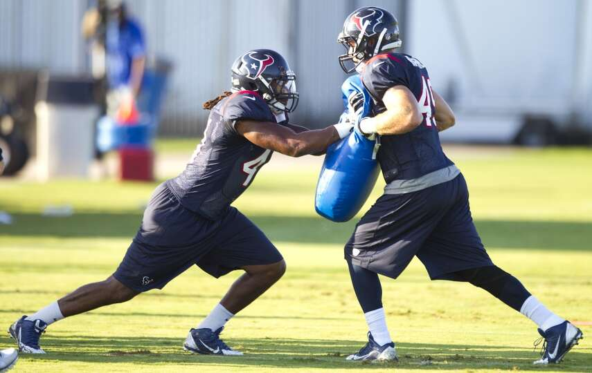 Linebackers Justin Tuggle, left, and Mike Mohamed (49) run a pass rush drill.