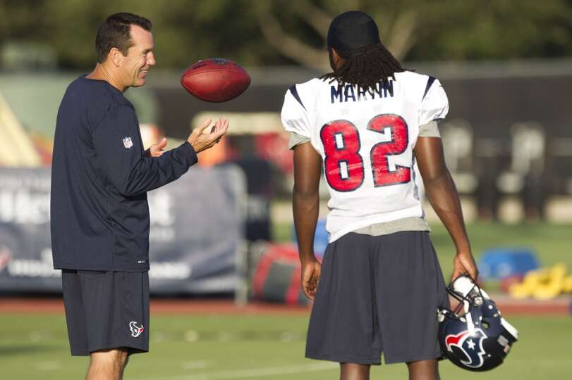 Head coach Gary Kubiak, left, talks to wide receiver Keshawn Martin (82) before practice.