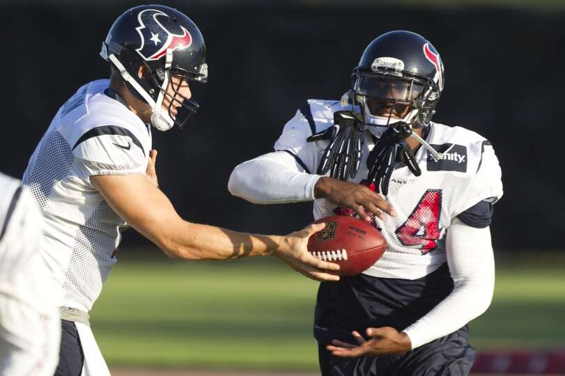 Quarterback Case Keenum, left, hands the ball off to running back Ben Tate.