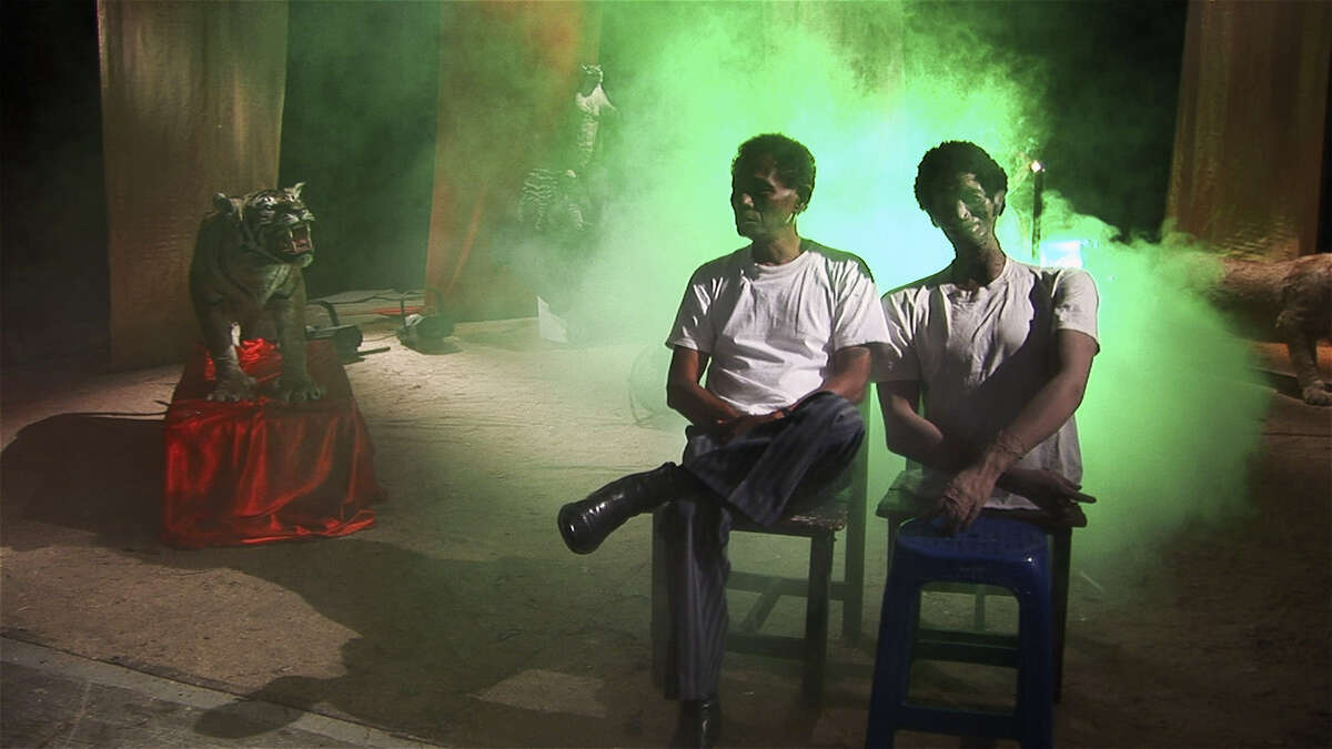 """Anwar (left), who offers lessons in death-squad techniques in """"The Act of Killing,"""" sits with a model of himself."""