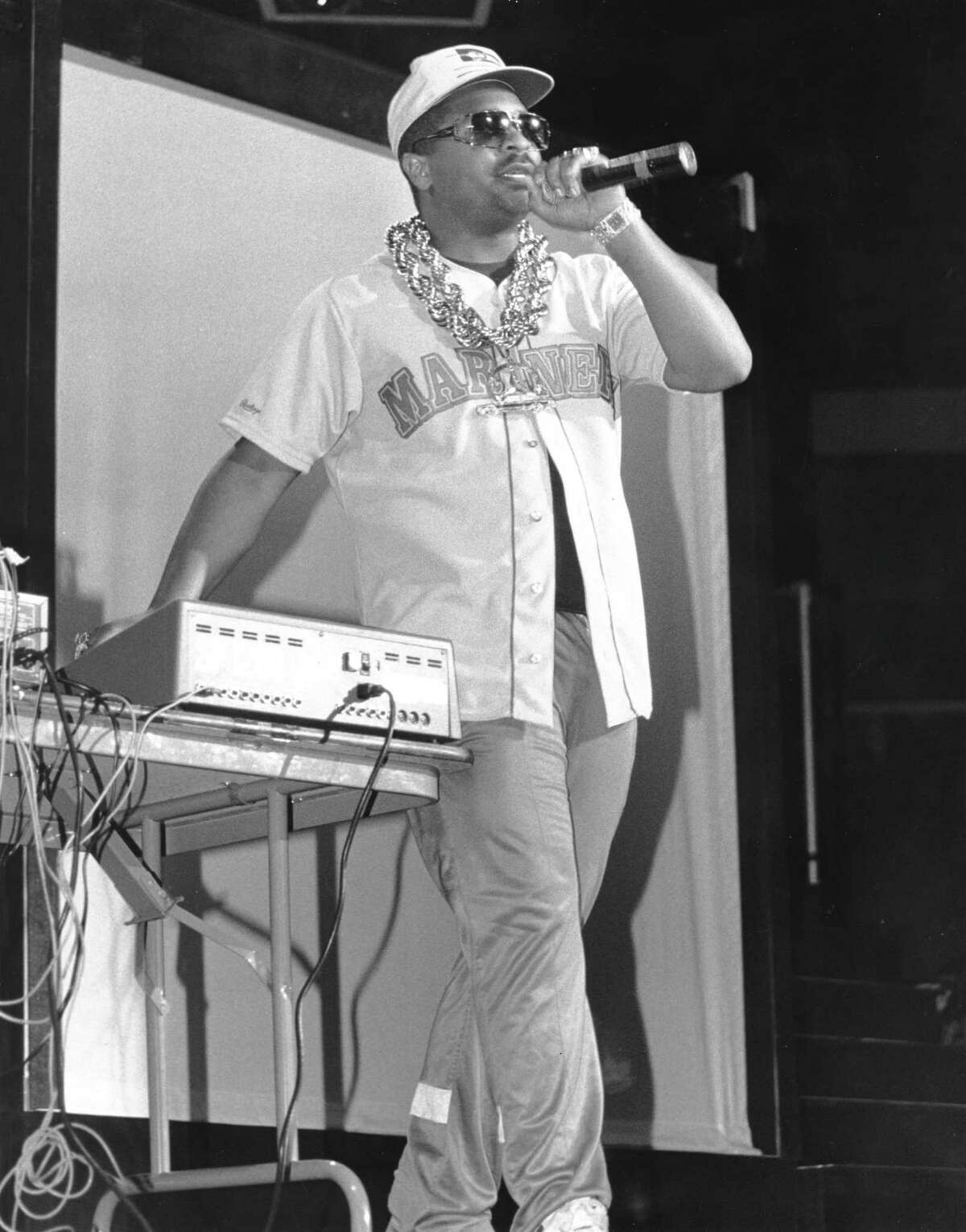 Sir Mix-A-Lot performs onstage wearing a Mariners jersey and a large gold chain in 1989.