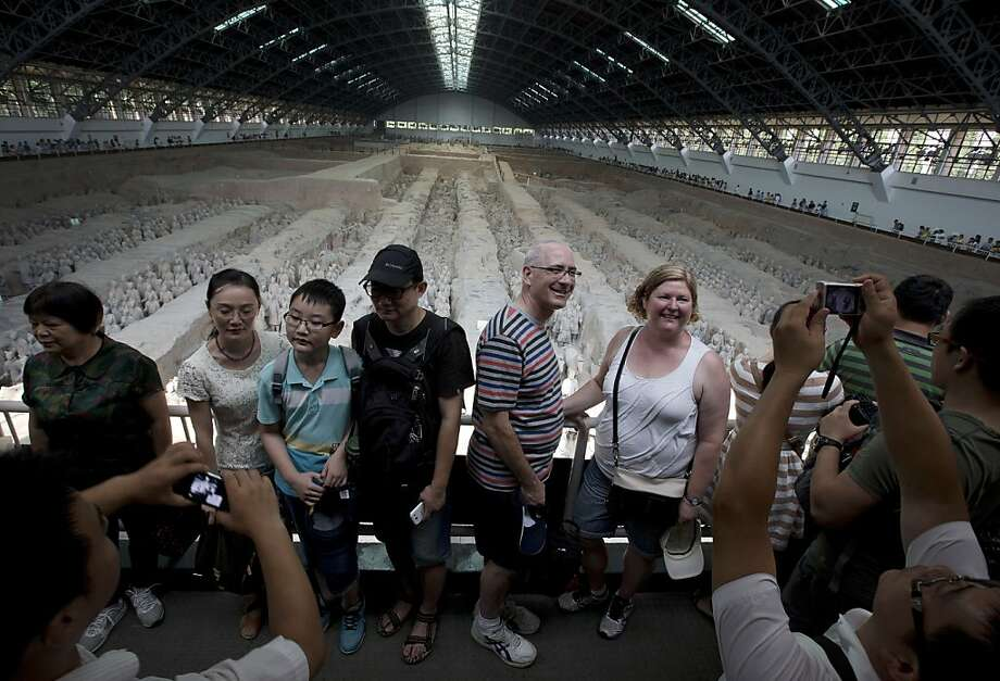 In this Tuesday, July 30, 2013 photo, foreign and local tourists have their souvenir photos taken near a display of the unearthed terracotta warriors as they visiting the excavation site inside the No.1 pit of the Museum of Qin Terracotta Warriors and Horses in Xi'an, in central China's Shaanxi province. China, one of the most visited countries in the world, has seen sharply fewer tourists this year ? with worsening air pollution partly to blame. (AP Photo/Andy Wong) Photo: Andy Wong, Associated Press