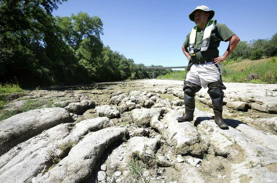 Vidal Mendoza, Hydrologic Technician with the USGS, inspects a dry river bed, the Guadalupe River, at the Spring Branch guage, on Tuesday, August 13, 2013. Photo: Bob Owen, San Antonio Express-News / © 2012 San Antonio Express-News