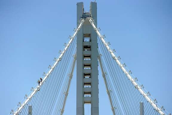 Workers walk up the suspension cable on the tower structure of the new eastern span of the Bay Bridge in Oakland, CA Saturday May 18th, 2013.