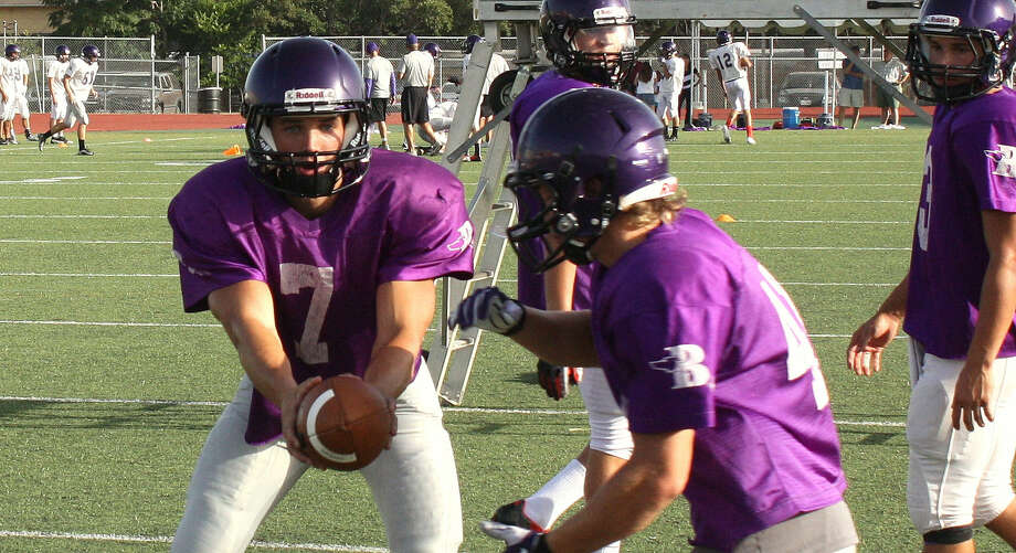 Boerne High School quarterback David Snelling (7) hands the ball off to running back Garrett Claunch during last Friday's first practice in pads at BISD Stadium.