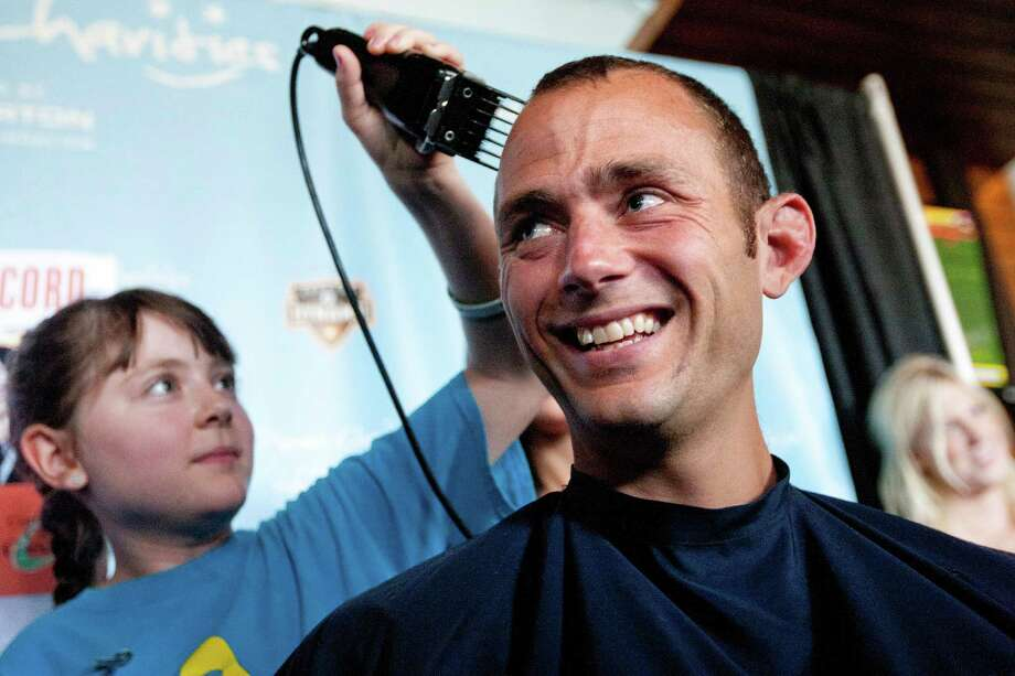 Kristina Barrett, 11, who has clear-cell sarcoma, shaves the head of the Houston Dynamo's Brad Davis during the fifth annual Bald is Beautiful campaign. Photo: Johnny Hanson, Houston Chronicle / © 2013  Houston Chronicle
