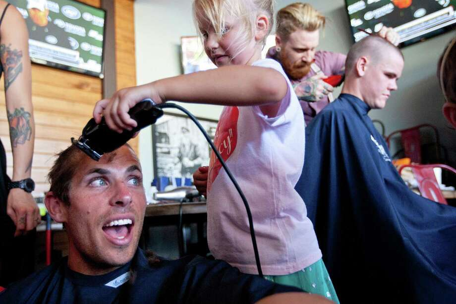 Lucy Schuler, 6, who is now recovered from having Acute Lymphoblastic Leukemia, shaves the head of Houston Dynamo goalie Tally Hall. Photo: Johnny Hanson, Houston Chronicle / © 2013  Houston Chronicle
