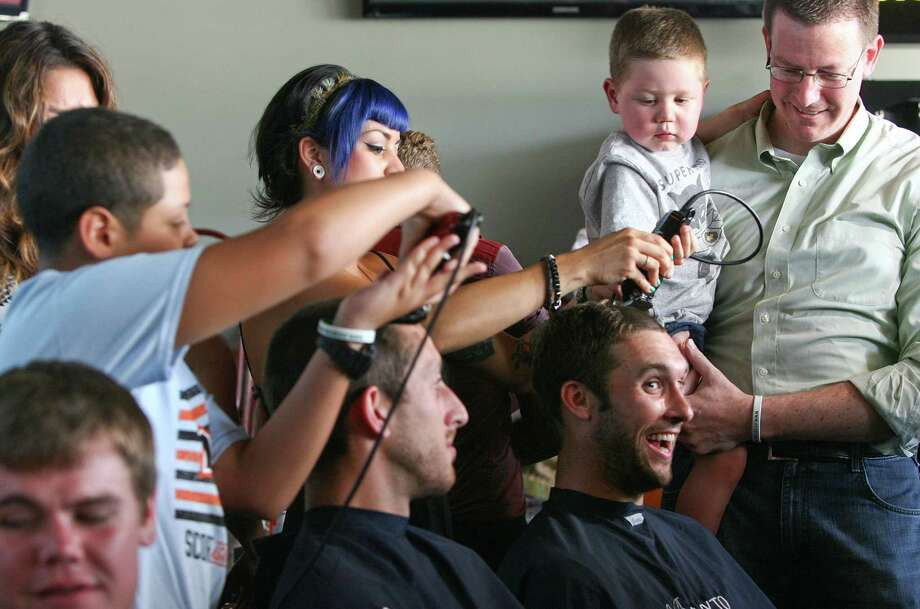 With the help of his father, Blake Ludban, Alex, 2, who is in remission from liver cancer, shaves the head of the Houston Dynamo's Will Bruin . Photo: Johnny Hanson, Houston Chronicle / © 2013  Houston Chronicle