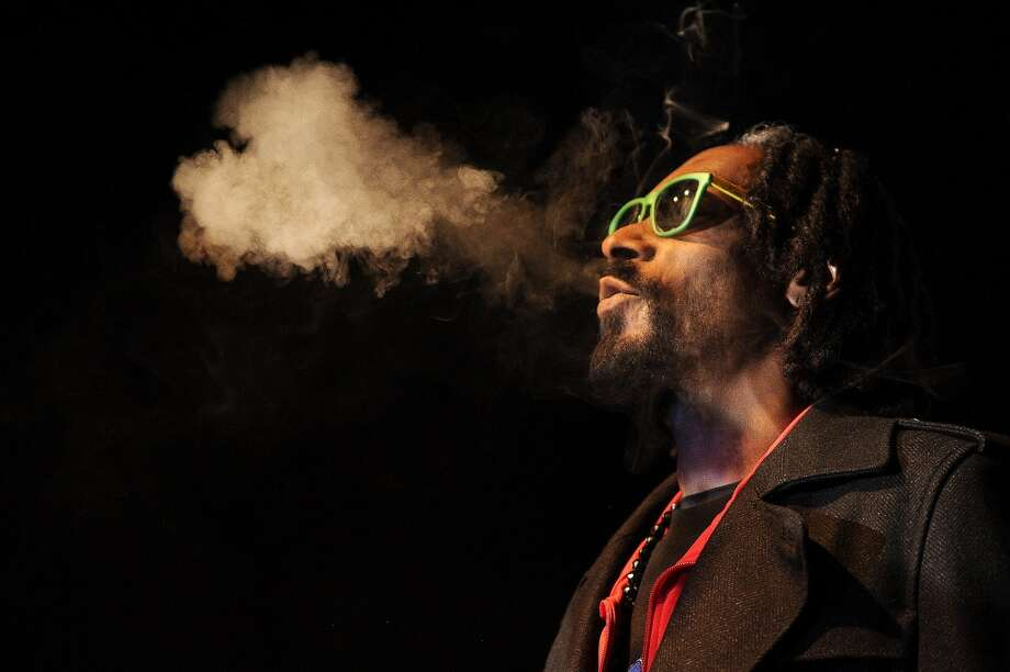 Snoop Dog, reincarnated as Snoop Lion, exhales a heart shaped cloud of marijuana smoke while doing a Q&A with the audience after the screening of his documentary Reincarnated during the first ever ''Green Carpet'' event as a part of the High Times US Cannabis Cup at the Fillmore Auditorium on April 19, 2013 in Denver, Colorado. (Photo by Seth McConnell/The Denver Post via Getty Images) Photo: Seth McConnell, Denver Post Via Getty Images