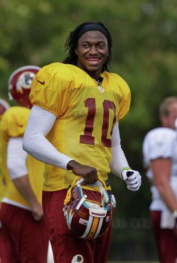 Washington Redskins quarterback Robert Griffin III smiles at fans during the afternoon session at NF