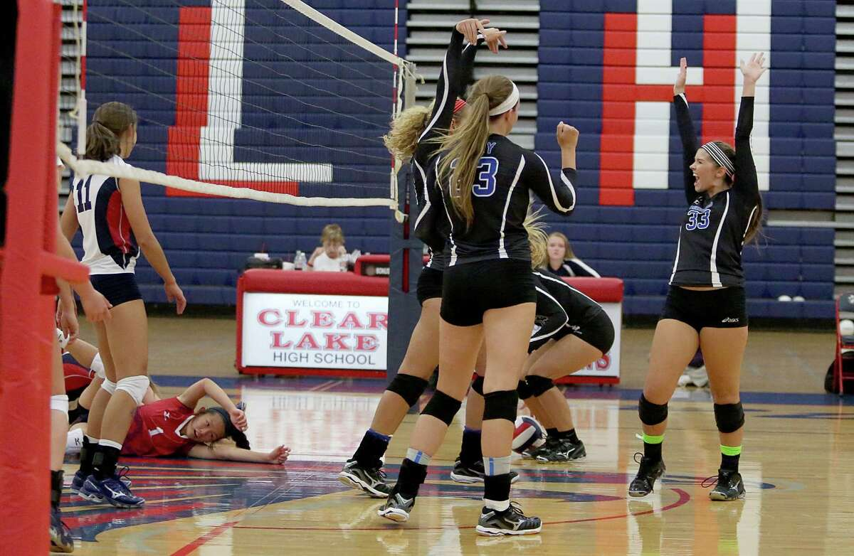 8/13/13: Friendswood Mustangs Kailyn Kelledy #33 and teammates celebrate a point against the Clear Lake Falcons in a high school volleyball match at Clear Lake High School in Houston, Texas.