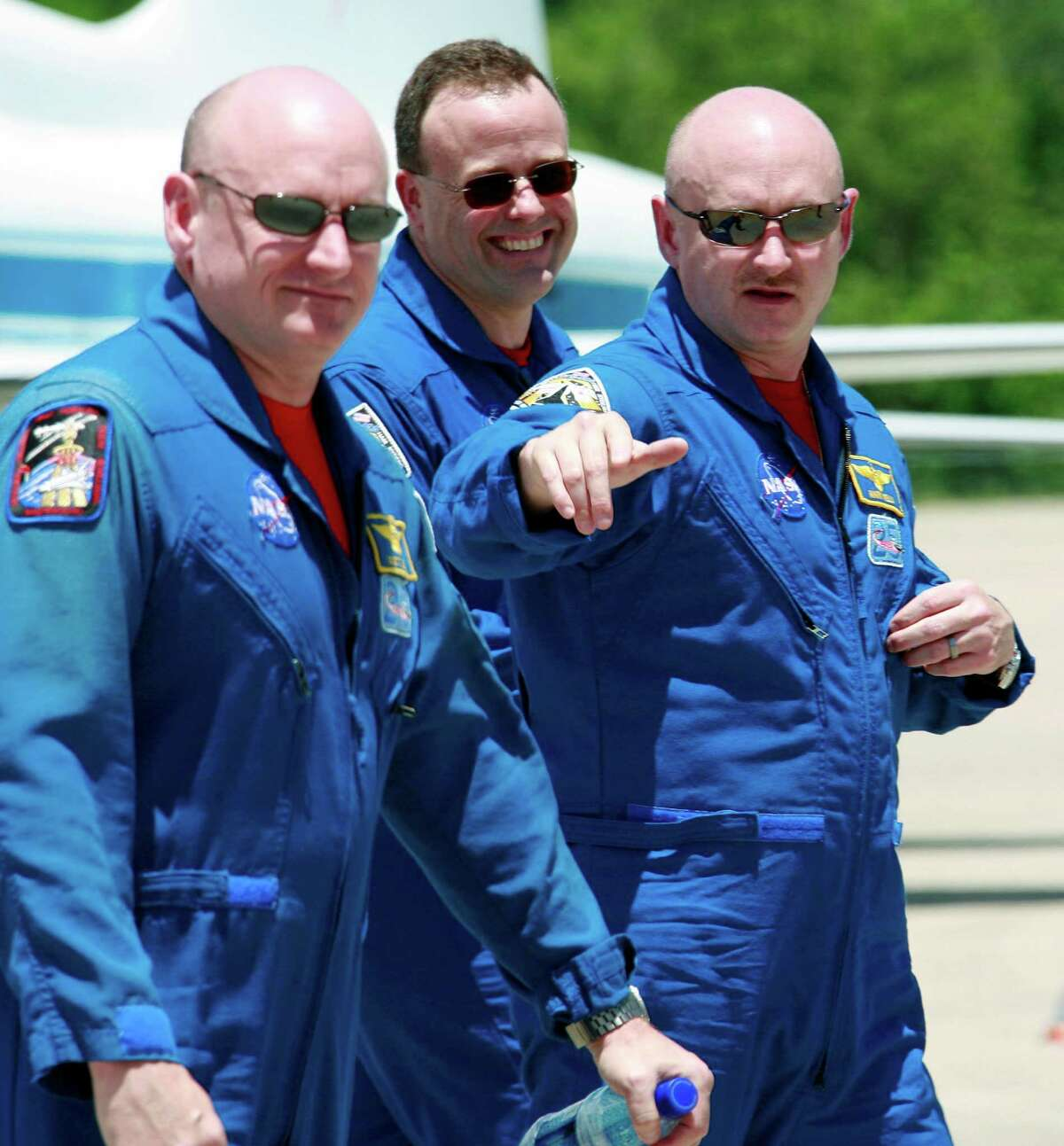 Scott Kelly, left, and his twin, former astronaut Mark Kelly - seen in 2011 with NASA mission specialist Ron Garan - will be part of a unique mission in 2015.