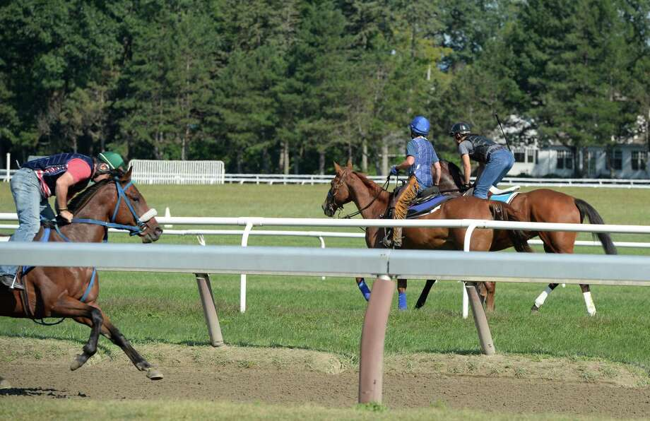 Tils Tilbury sits atop her pony Frosty, center, as she ponies a horse and rider to the Oklahoma Training Center Monday morning, Aug. 12, 2013, in Saratoga Springs, N.Y.   (Skip Dickstein/Times Union) Photo: SKIP DICKSTEIN