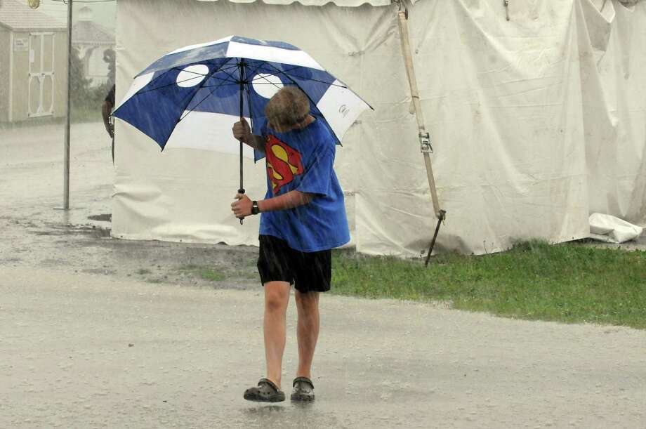 David Huse of Guilderland makes his way through the rain during the Altamont Fair on Tuesday Aug. 13, 2013 in Altamont, N.Y. (Michael P. Farrell/Times Union) Photo: Michael P. Farrell / 00023489A