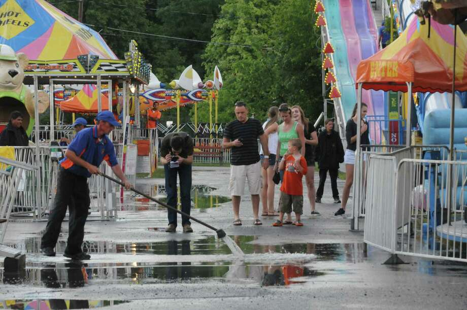Crews clean up standing water after an early evening torrential rain during the Altamont Fair on Tuesday Aug. 13, 2013 in Altamont, N.Y. (Michael P. Farrell/Times Union) Photo: Michael P. Farrell / 00023489A