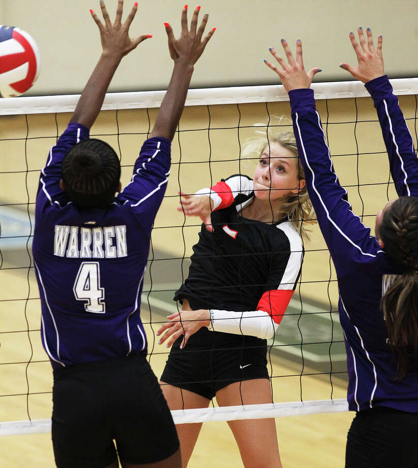 Churchill's Amy Nettles (05) hits against Warren's Bobbie Barnes (04) in volleyball at Littleton Gym on Tuesday, Aug. 13, 2013. Photo: Kin Man Hui, San Antonio Express-News / ©2013 San Antonio Express-News