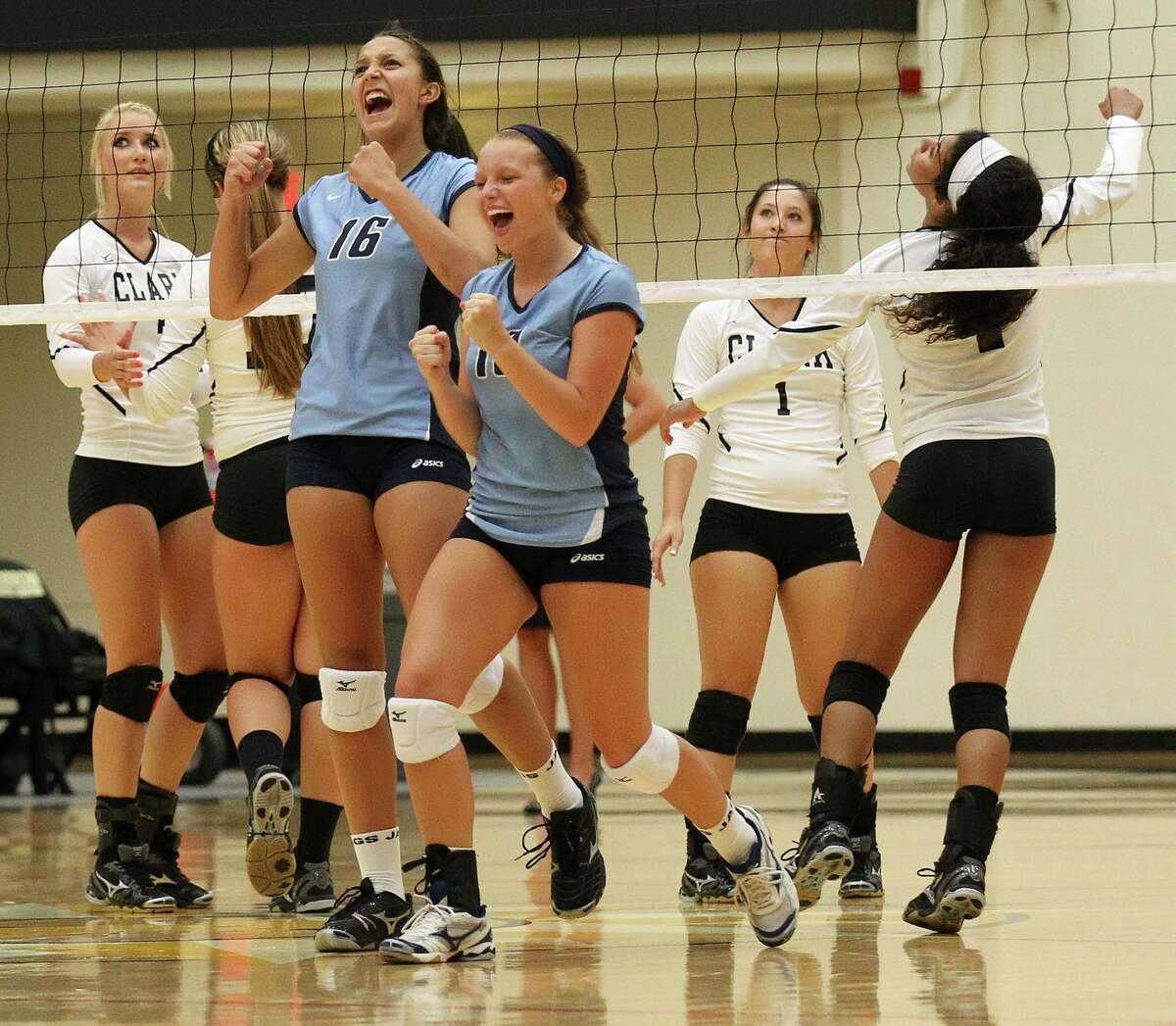 Johnson's Lauren Bault (16) and Meghan Parker (10) react after winning a point against Clark in volleyball at Littleton Gym on Tuesday, Aug. 13, 2013.