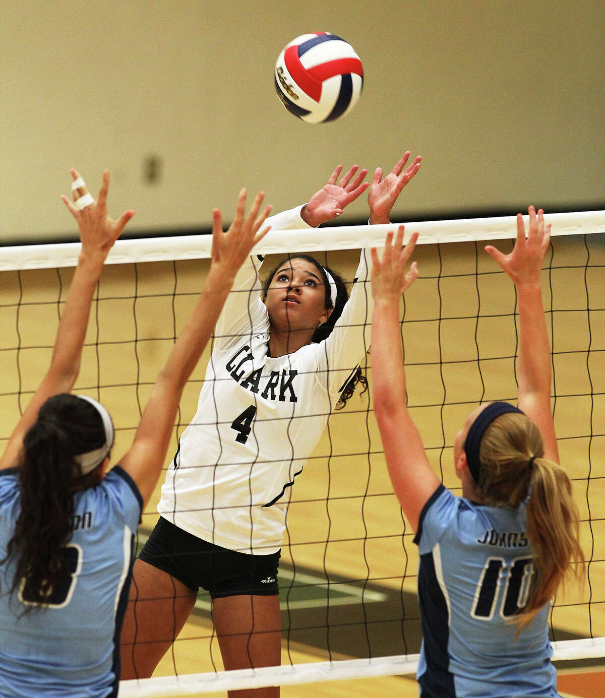 Clark's Maddie Woods (04) attempts a play against Johnson's Shelby Walker (08) and Meghan Parker (10) in volleyball at Littleton Gym on Tuesday, Aug. 13, 2013.
