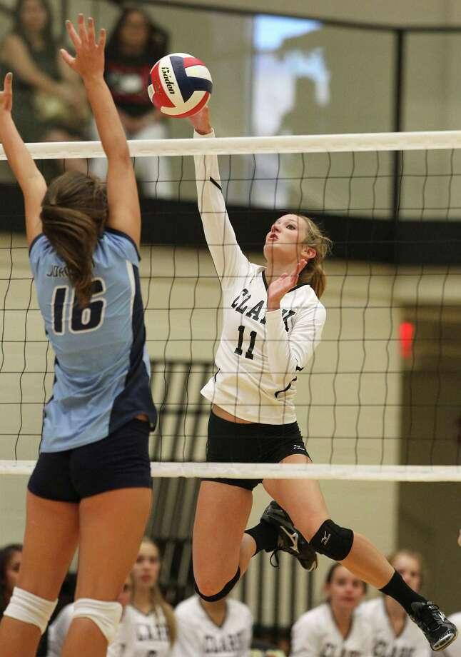 Clark's Katie Mattson (11) goes for a shot against Johnson's Lauren Bault (16) in volleyball at Littleton Gym on Tuesday, Aug. 13, 2013. Photo: Kin Man Hui, San Antonio Express-News / ©2013 San Antonio Express-News