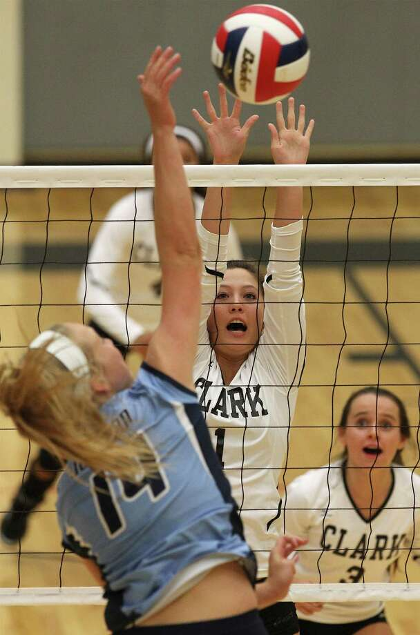 Clark's Kelly Cavanaugh (01) reaches to attempt a block against Johnson's Kylie Rittimann (14) in volleyball at Littleton Gym on Tuesday, Aug. 13, 2013. Photo: Kin Man Hui, San Antonio Express-News / ©2013 San Antonio Express-News