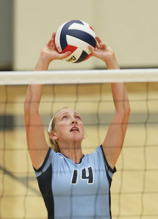 Johnson's Kylie Rittimann (14) sets up a play against Clark in volleyball at Littleton Gym on Tuesday, Aug. 13, 2013. Photo: Kin Man Hui, San Antonio Express-News / ©2013 San Antonio Express-News