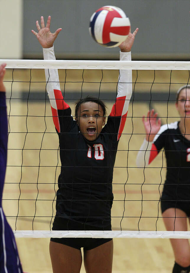 Churchill's Dariann Gilford (10) reaches for a block against Warren in volleyball at Littleton Gym on Tuesday, Aug. 13, 2013. Photo: Kin Man Hui, San Antonio Express-News / ©2013 San Antonio Express-News